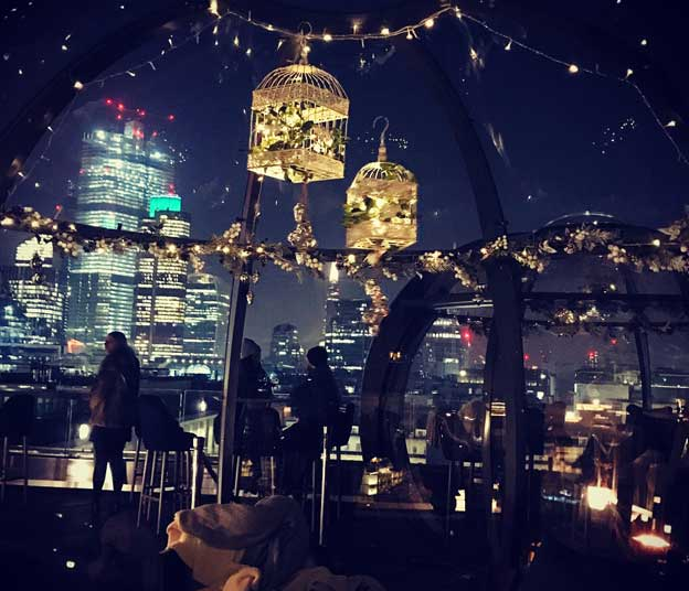 A nighttime city view from inside a rooftop dining igloo