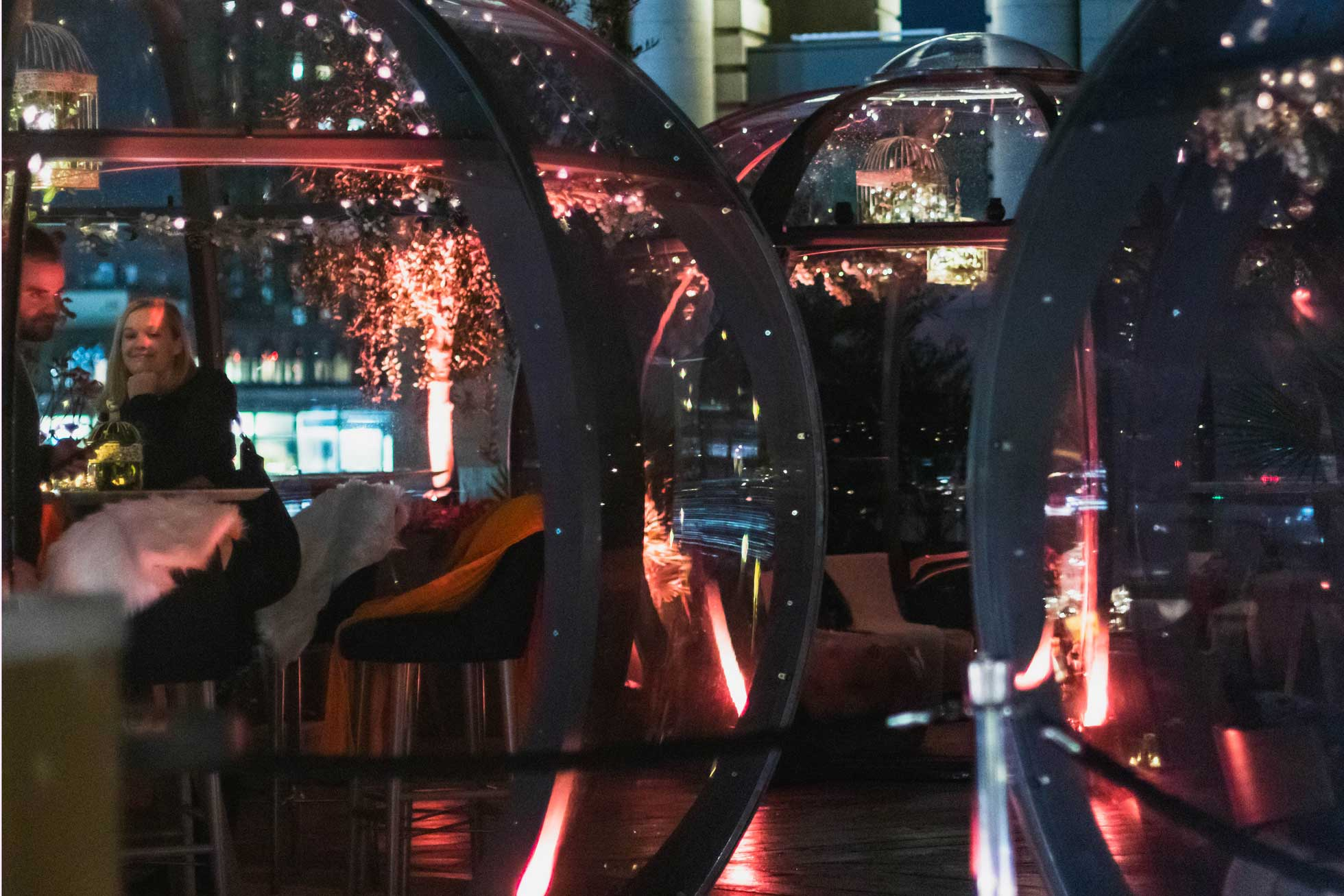 Patrons enjoy their drinks and the ambience from one of several pods decorated with pretty lights
