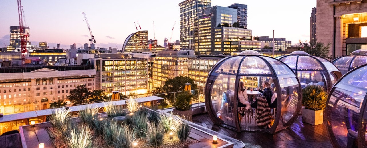 A dramatic cityscape evening view with customers enjoying refreshments in rooftop pods