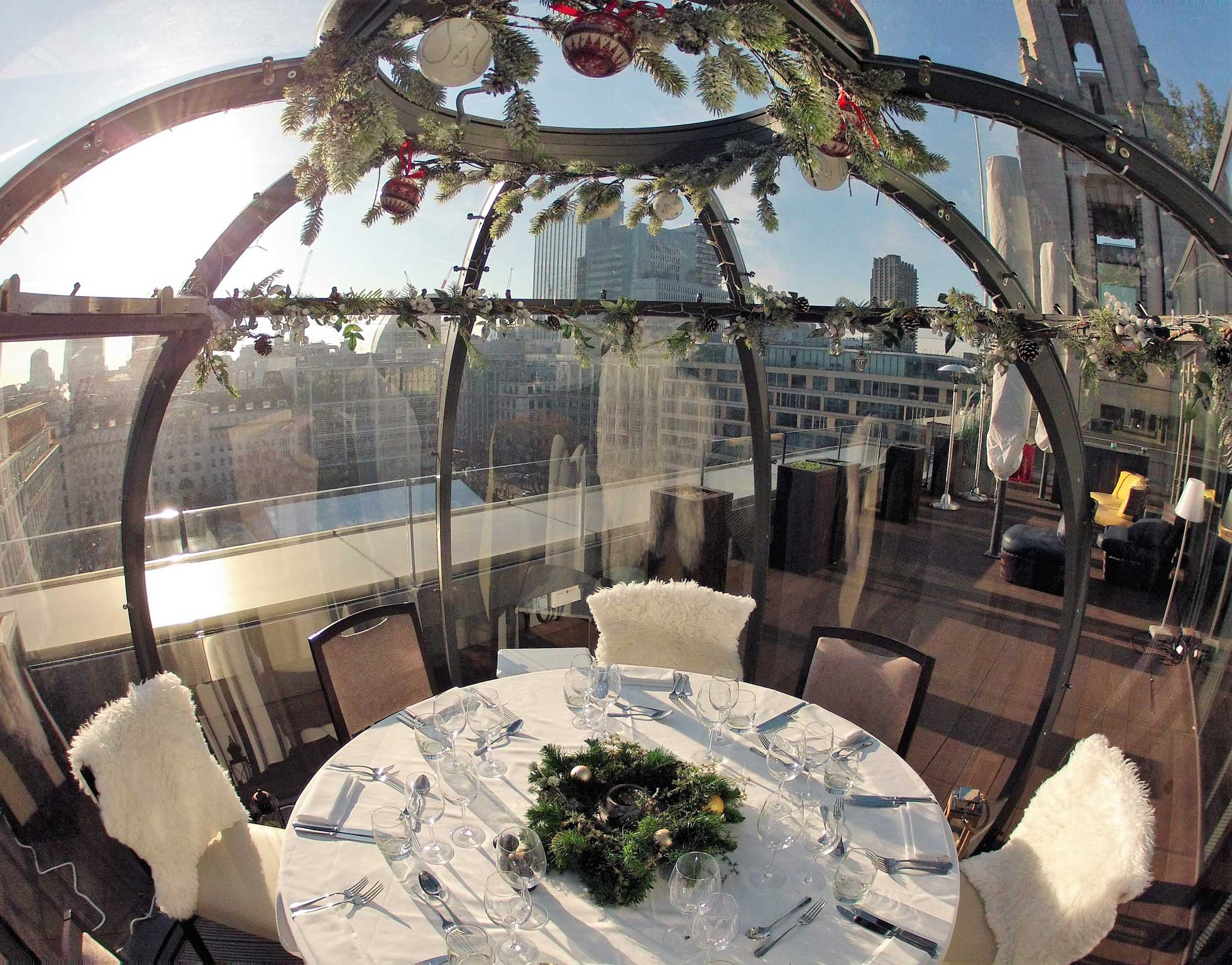 Interior shot from within a rooftop dining pod on a clear sunny day with cityscape